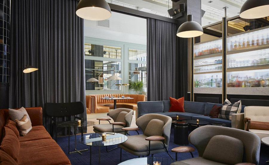 Restaurant seating area furnished with orange bar furniture and blue sofas